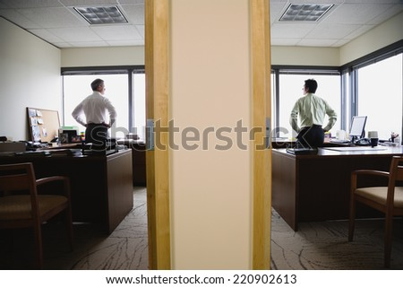 Two businessmen in neighboring offices - stock photo