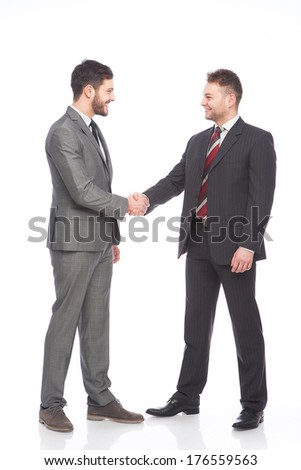 two businessmen in suits shaking hands and smiling on white background - stock photo