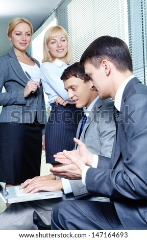 Two businessmen interacting while working with laptop on background of pretty females looking at them - stock photo