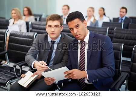 Two businessmen looking at camera at seminar on background of their colleagues - stock photo