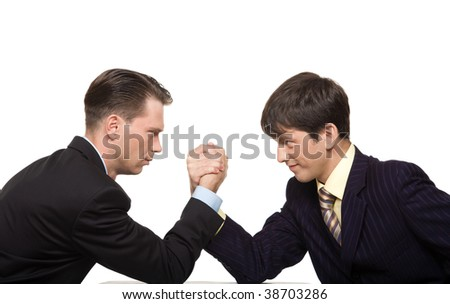 Two businessmen looking at each other seriously while doing arm wrestling - stock photo