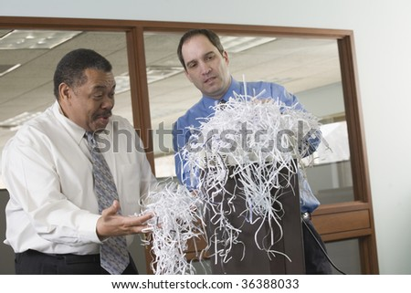 Two businessmen looking at shredded papers - stock photo