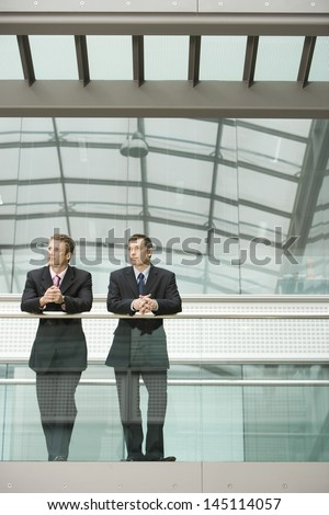 Two businessmen looking away while standing against glass railing in office - stock photo
