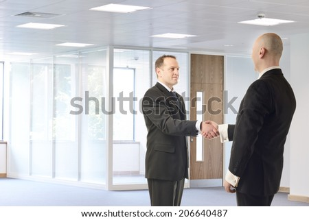 Two businessmen meeting in a brightly lit office space - stock photo