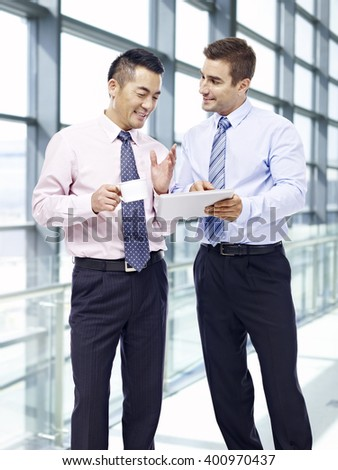 two businessmen, one asian and one caucasian, having a discussion while waiting for flight at airport. - stock photo