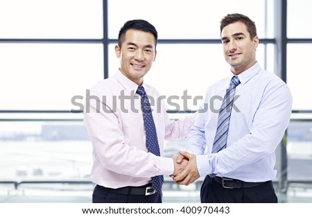 two businessmen, one asian and one caucasian, shaking hands looking at camera at modern airport. - stock photo