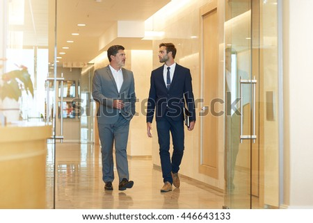 Two businessmen, one young and one mature, talking seriously while walking together in a modern office building foyer - stock photo
