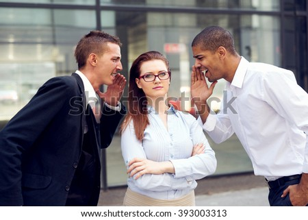 Two businessmen screaming at business woman. - stock photo