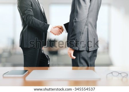 Two businessmen shake hands in the office - stock photo