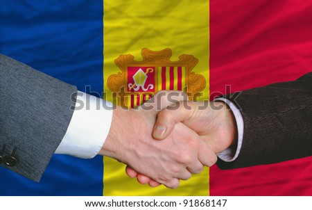 two businessmen shaking hands after good business investment  agreement in andorra, in front of flag - stock photo