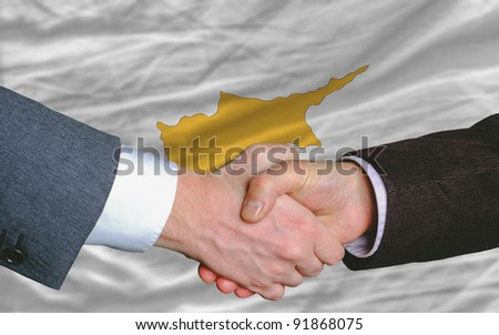 two businessmen shaking hands after good business investment  agreement in cyprus, in front of flag - stock photo