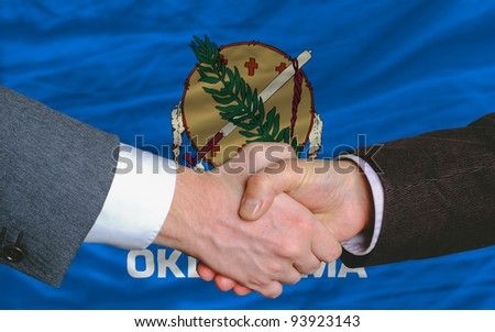 two businessmen shaking hands after good business investment agreement in front US state flag of oklahoma - stock photo