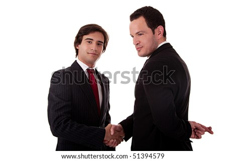 two businessmen shaking hands, and one businessman with his fingers crossed behind his back and smiling, isolated on white background - stock photo