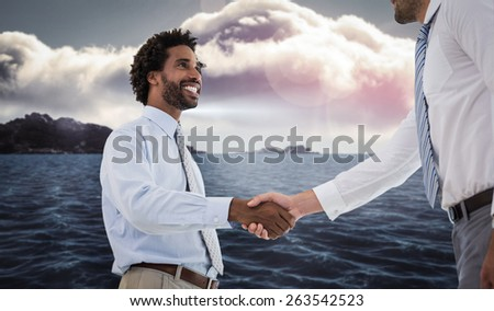 Two businessmen shaking hands in office against calm sea with lighthouse - stock photo