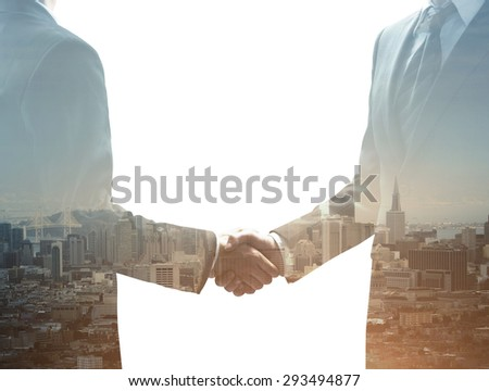 two businessmen shaking hands on city background - stock photo