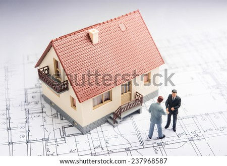 Two businessmen shaking hands on top architectural plans - stock photo