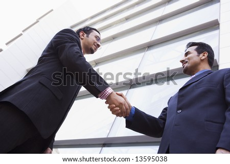 Two businessmen shaking hands outside modern office building - stock photo