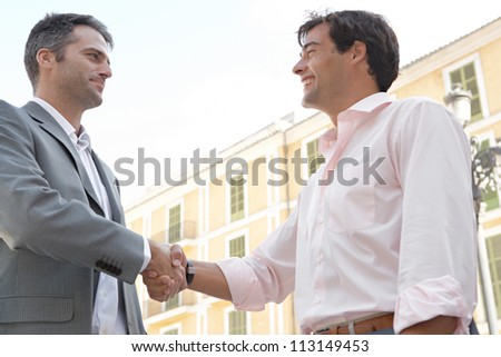 Two businessmen shaking hands while standing in front of a classic European building, outdoors. - stock photo
