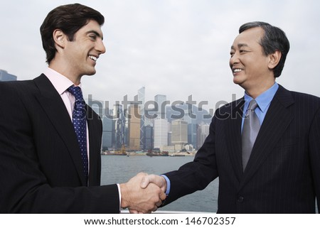 Two businessmen shaking hands with cityscape in background - stock photo