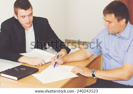 Two businessmen sitting at a desk discussing a contract or agreement going through the fine print together - stock photo