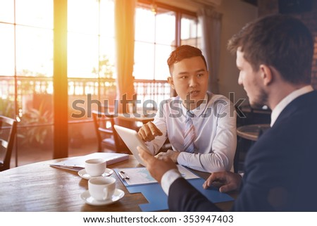Two businessmen sitting in cafe and discussing business project - stock photo