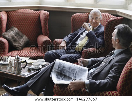 Two businessmen sitting in office lobby and communicating - stock photo
