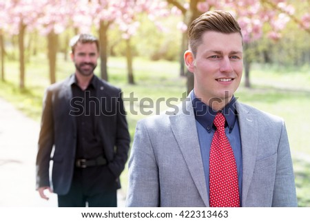 two businessmen standing in park in front of cherry blossom - stock photo