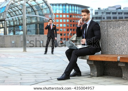 Two businessmen talking on the phone - stock photo