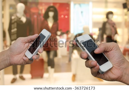 Two businessmen using mobile smart phone with blurred fashion displayed in department store, communication concept, transfer concept. - stock photo