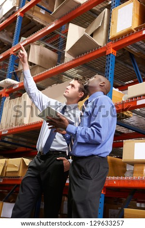 Two Businessmen With Digital Tablet In Warehouse - stock photo