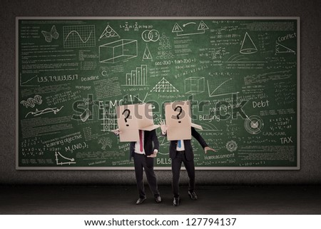 Two businessmen with question mark boxes standing in front of blackboard - stock photo