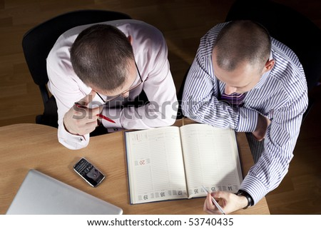 Two businessmen working at notebook - stock photo