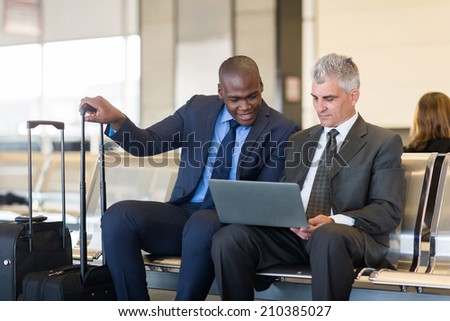two businessmen working on laptop computer at airport - stock photo