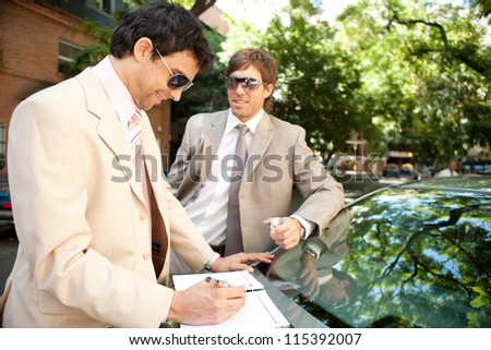 Two businessmen working while leaning on a luxury car in a tree lined street in the city. - stock photo