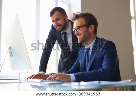 Two businessmen working with computer in office - stock photo
