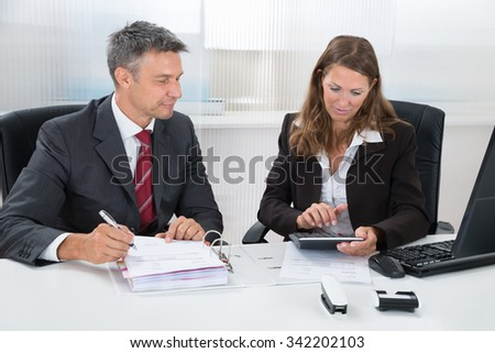 Two Businesspeople Calculating Tax Together At Desk In Office - stock photo