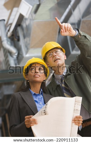 Two businesspeople in hard hats holding blueprints - stock photo