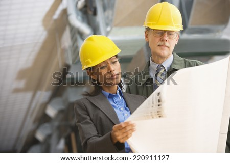 Two businesspeople in hard hats looking at blueprints - stock photo