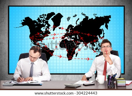 two businesspeople in office and international flights scheme on screen - stock photo