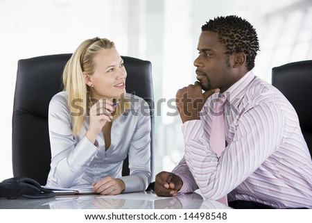 Two businesspeople in office talking - stock photo