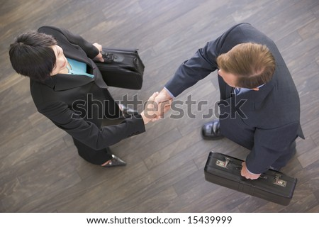 Two businesspeople indoors shaking hands - stock photo