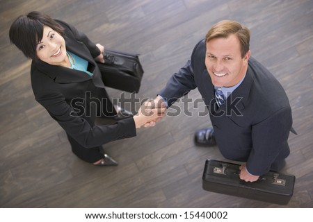 Two businesspeople indoors shaking hands smiling - stock photo