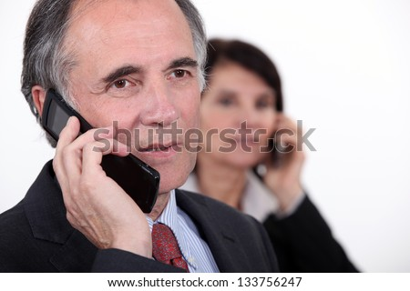 Two businesspeople making phone calls - stock photo