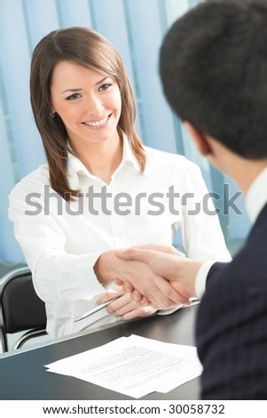 Two businesspeople, or business person and client handshaking at office - stock photo