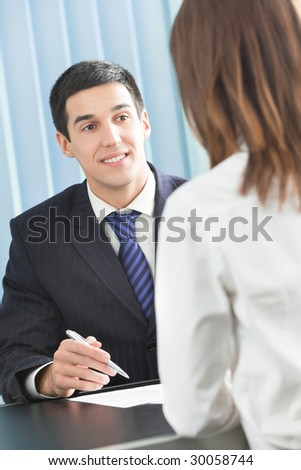 Two businesspeople, or businessman and client, with document at office - stock photo
