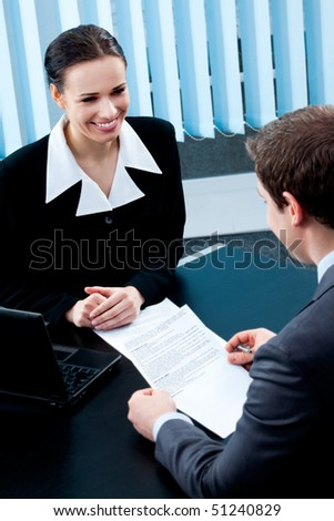 Two businesspeople, or businesswoman and client, with document at office - stock photo