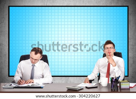 two businesspeople sitting in office and signing of a treaty - stock photo