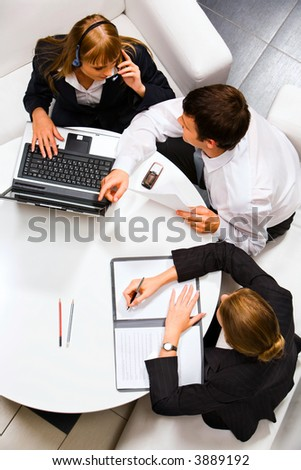 Two businesspeople sitting on the white sofas at the round table and discussing questions - stock photo