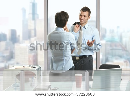 Two businesspeople standing at desk in downtown office building, talking and smiling. - stock photo