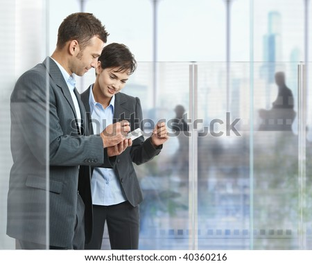 Two businesspeople standing in modern office with glass walls, looking at smart mobile phone. - stock photo